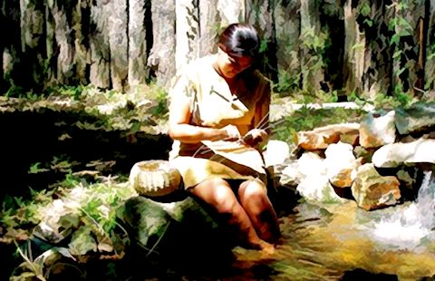 A Cherokee woman weaves a basket.
