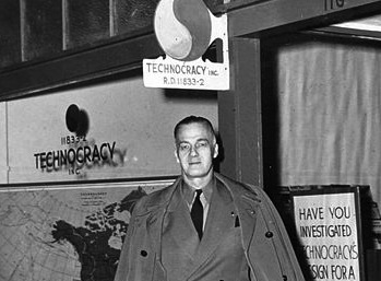 Howard Scott, Technocracy leader, poses in front of a sign.